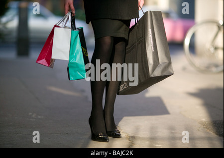 shopping bags from exclusive shops carried by a young woman in Soho London - Stock Photo