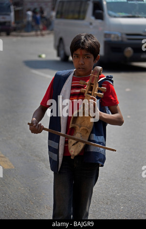 Young boy playing violin musical instrument in street for tourist begging money, Nepal Kathmandu - Stock Photo