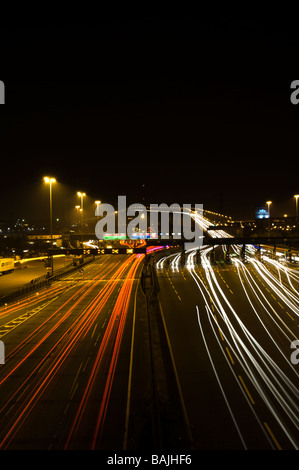 Night time photograph of the Dartford River Crossing (QE2 Bridge) showing headlamp and tail light trails. - Stock Photo