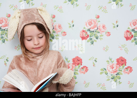 Young girl (5-6) n bunny costume reading book, wallpaper with floral pattern in background - Stock Photo