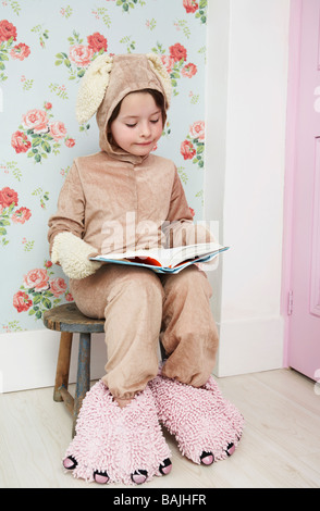 Young girl (5-6) sitting on stool reading, wearing bunny costume and monster slippers - Stock Photo