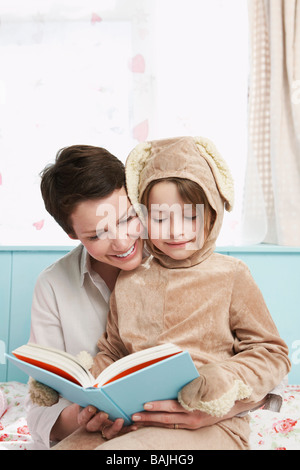 Mother and daughter (5-6) in bedroom reading book, girl in bunny costume - Stock Photo