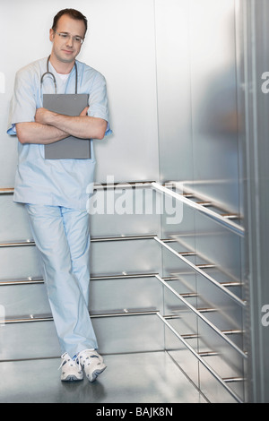 Physician Waiting in Elevator - Stock Photo