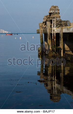 View across still sea to lobster pots on a jetty at Swanage, Dorset, England, UK - Stock Photo