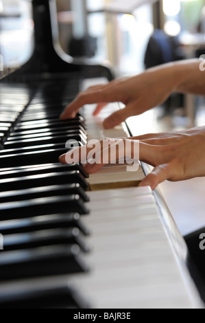 Close-up of hands playing a grand piano - Stock Photo