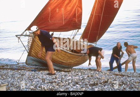 Hauling in a Beer lugger sailing boat at Beer beach Devon England UK Europe - Stock Photo