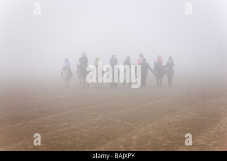 Donkey riders emerging from the sea mist on the beach in Weston super Mare - Stock Photo