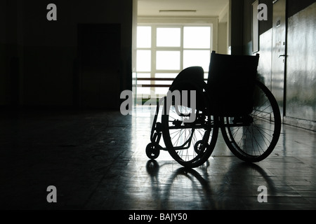 Silhouette of empty wheelchair parked in hospital hallway - Stock Photo