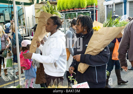 Two young women buying flowers in Columbia Road Sunday flower market - Stock Photo