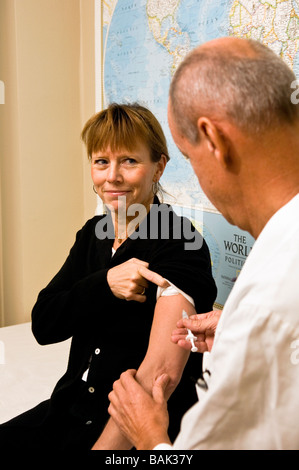 Doctor gives a female patient a vaccination shot against flu - Stock Photo