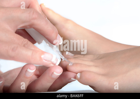 Beautician applying nail polish to toes in a spa model release available - Stock Photo