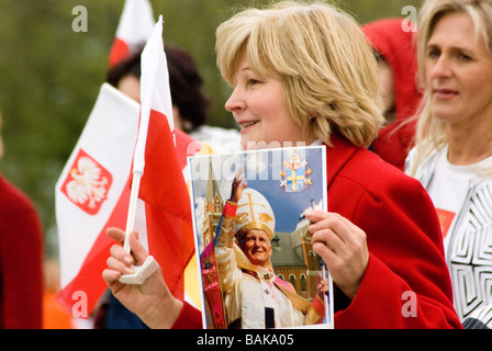 Middle aged woman carries photo of Pope and waves flag in Chicago Polish Parade - Stock Photo