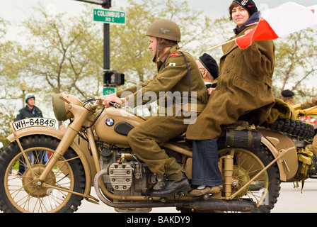 Man and woman in vintage Polish army uniform clothing riding antique motorcycle in Chicago Polish Parade - Stock Photo