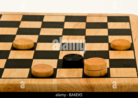Checkers on a checkerboard at the end of the game - Stock Photo