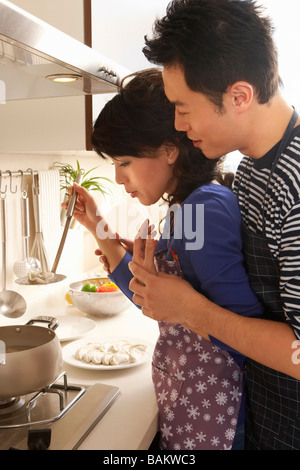 Young Couple Blow On A Hot Dumpling Straight From The Pot - Stock Photo