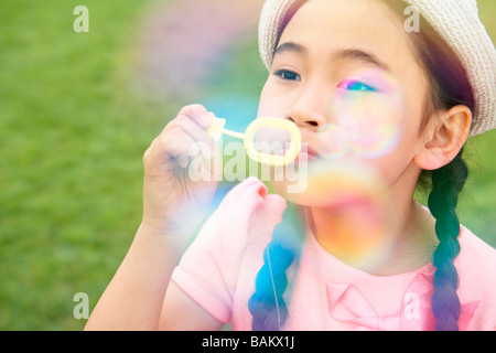 Little Girl Blowing Bubbles - Stock Photo