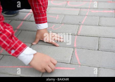 Boy Drawing On Sidewalk With Chalk - Stock Photo