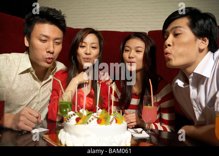 Group of Young People Blowing Out Candles On Birthday Cake - Stock Photo