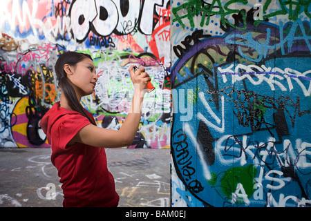 A young woman spraying graffiti - Stock Photo