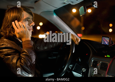 Man on cellphone in car - Stock Photo