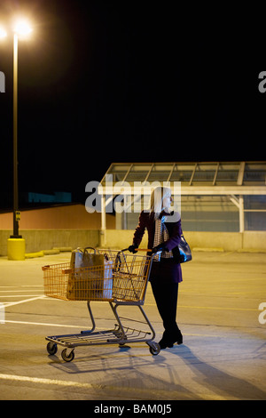 Woman alone in supermarket parking lot - Stock Photo