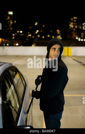 Thief breaking into car - Stock Photo
