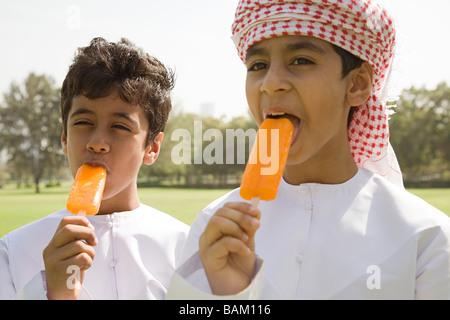 Two boys having ice lollies - Stock Photo