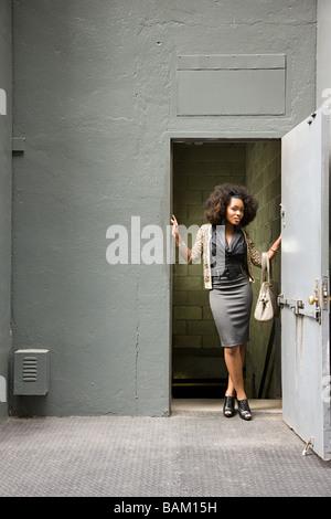 Young woman in doorway - Stock Photo