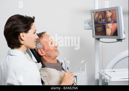 Dentist and patient looking at monitor - Stock Photo