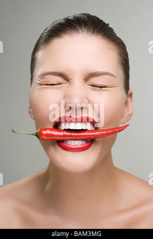 Woman biting a red chili pepper - Stock Photo
