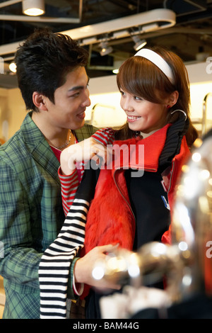 Young Couple Looking At Each Other, Holding Up Clothes - Stock Photo