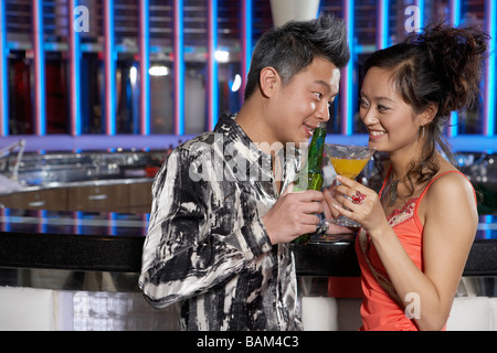 Couple Leaning Against The Bar In A Nightclub - Stock Photo