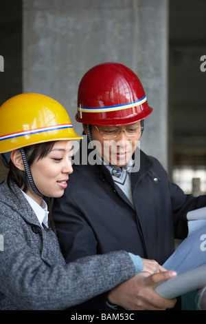 Businesspeople In Construction Site Wearing Hard Hats - Stock Photo