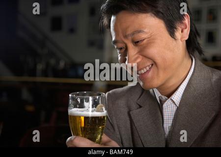 Happy Businessman Holding Beer - Stock Photo