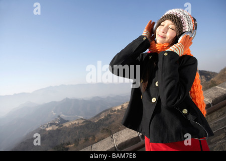 Young Woman Listening To Headphones On The Great Wall Of China - Stock Photo