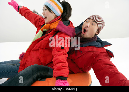 Couple Riding On Inflatable Snow Tube - Stock Photo