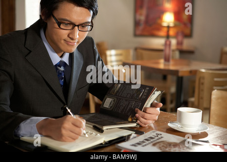 Businessman Writing In A Book - Stock Photo