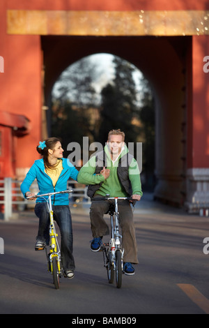 Couple Riding Bicycles, Smiling At Each Other - Stock Photo