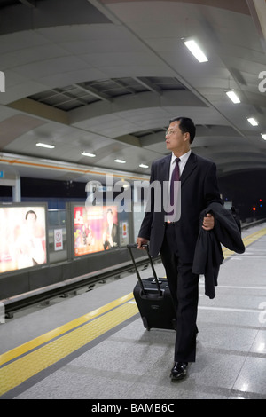 Businessman Pulling Suitcase Along In Train Station - Stock Photo