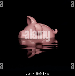 Pink piggy bank sinking in water Stock Photo