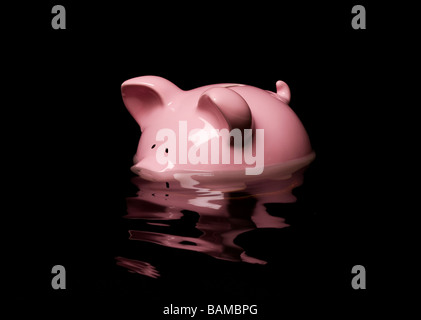 Pink piggy bank sinking in water - Stock Photo