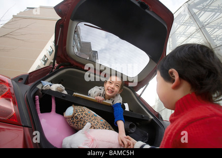 Boy And Girl Playing In And Around Car - Stock Photo