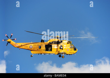 Helicopter Sea King Search and Rescue RAF SARS yellow flying side view blue sky white cloud - Stock Photo