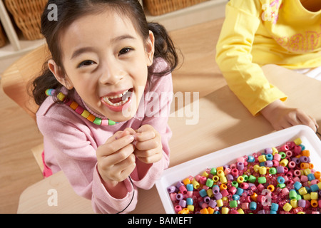 Girl In Classroom Laughing And Playing With Beads - Stock Photo
