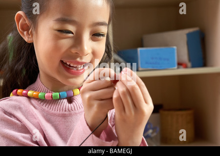 Girl In Classroom Smiling And Playing With Bead Necklace - Stock Photo