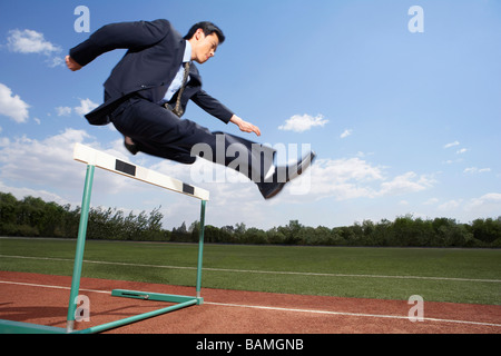 Businessman In His Suit Jumping A Hurdle - Stock Photo