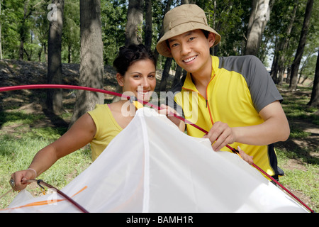 Young Couple Setting Up A Tent While Camping - Stock Photo