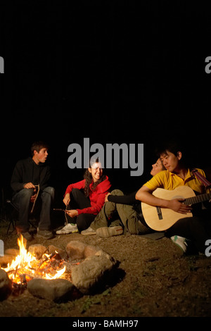 Young People Sitting Around Campfire - Stock Photo
