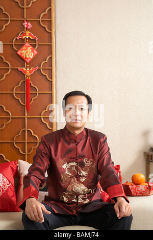 Portrait Of Man Sitting On The Couch Wearing Traditional Clothing - Stock Photo