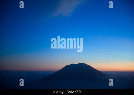 The peak of Mount Agung seen from a airplane window rises 10 308 feet above sea level - Stock Photo